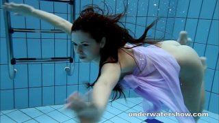 امرأة شابة جميلة تقفز إلى المسبح وتحب السباحة عارية وتصويرها